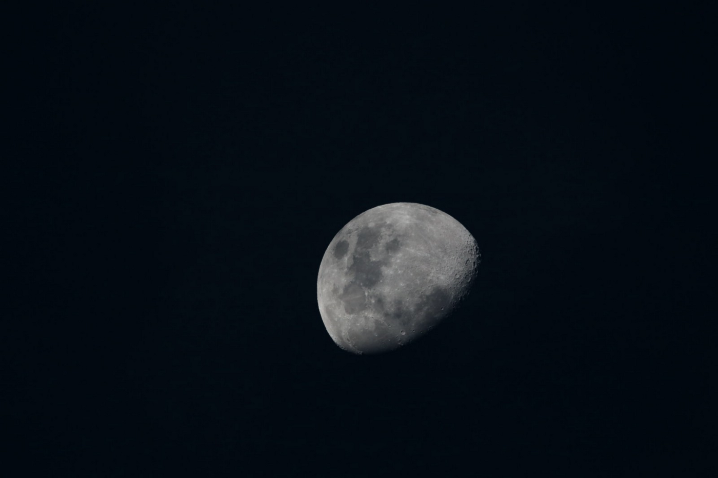 A solitary three quarter moon on a pitch black background in black and white.
