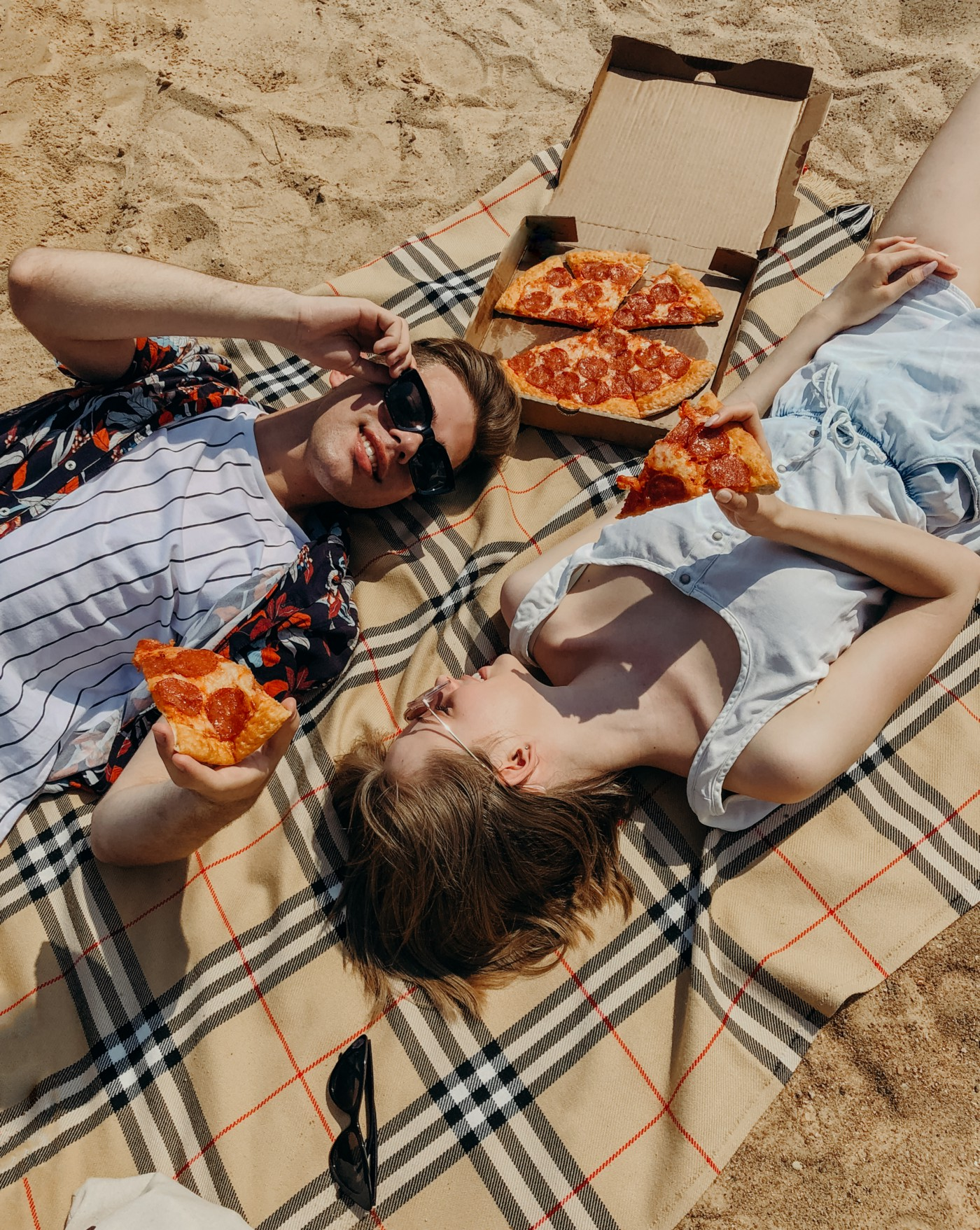 Picture of 2 people having pizza in the sun.
