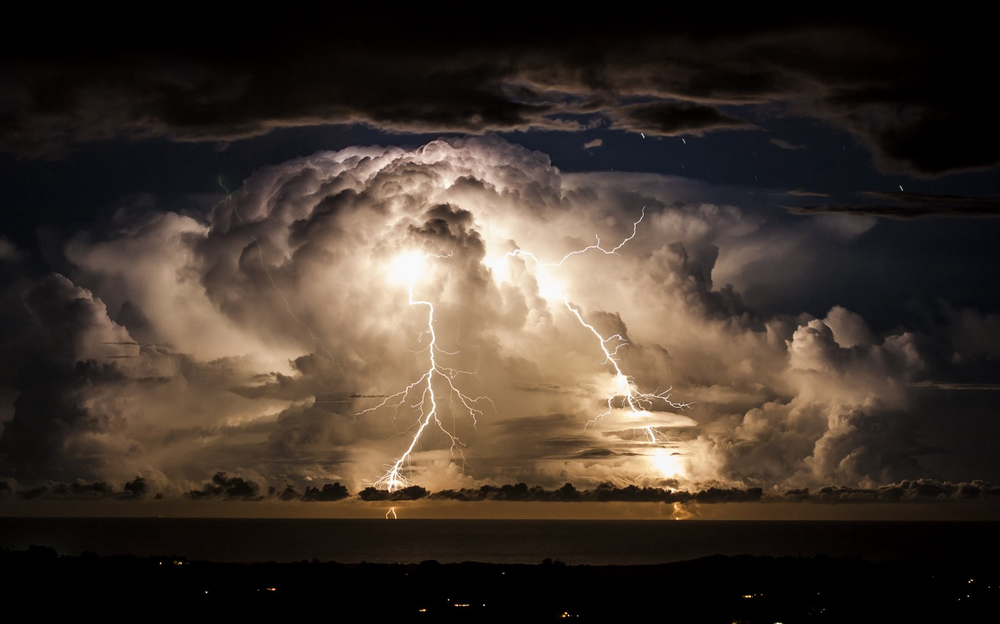 Storm clouds shroud an electrical storm of the coast of Byron Bay at night.