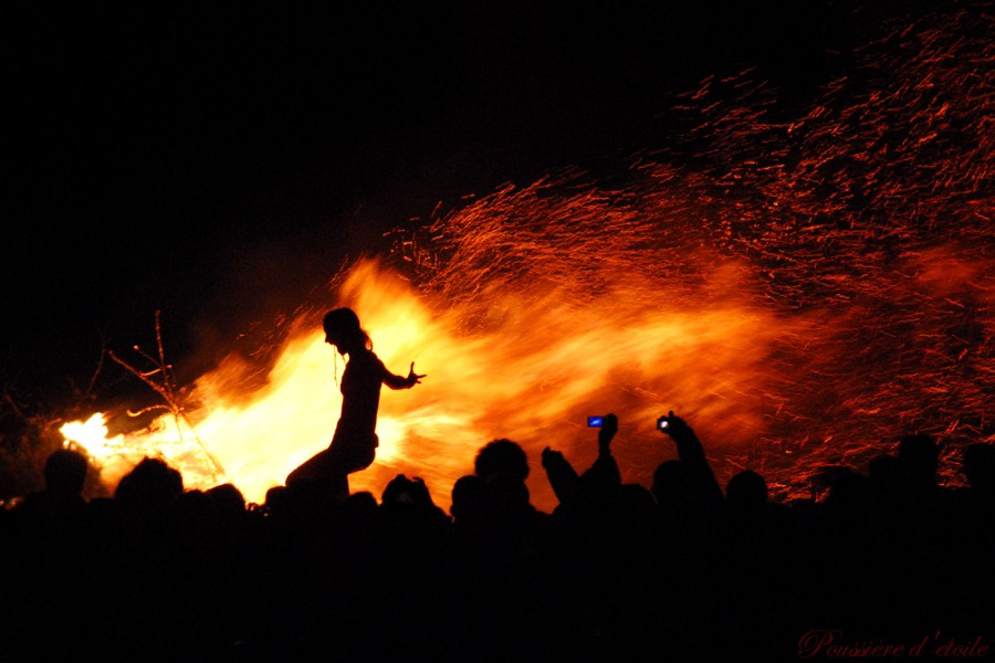 Borne aloft on a crowd, a man basks in the flames of a raging Beltane fire.