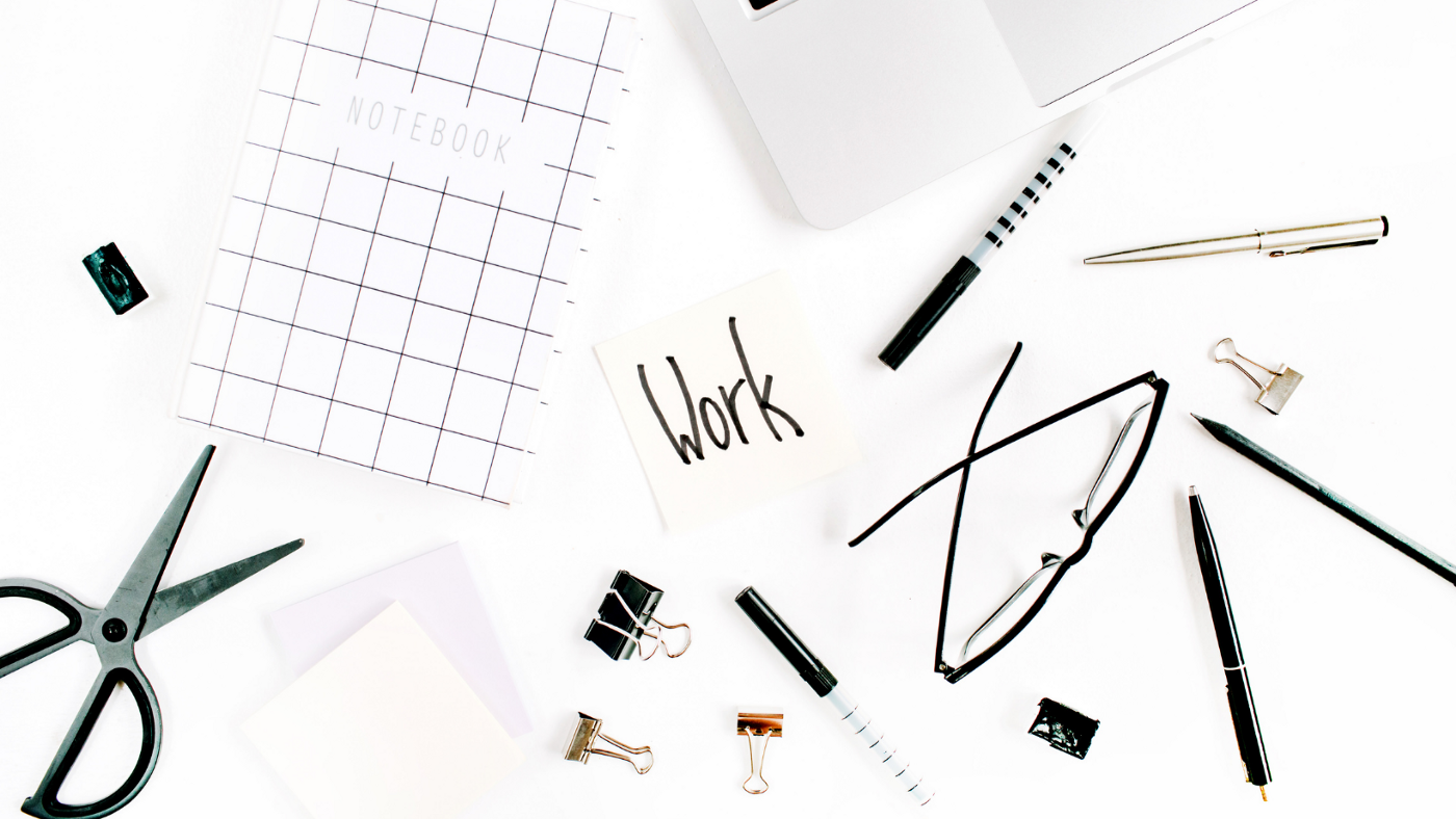 "A picture with the word ""work"" in the middle, surrounded by work items such as a pen, notebook, glasses, clips, etc… on a white desk"