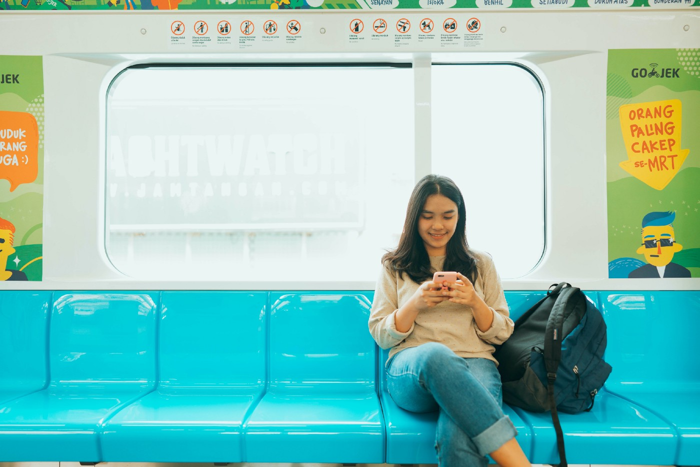 woman sitting in subway looking at her cell phone