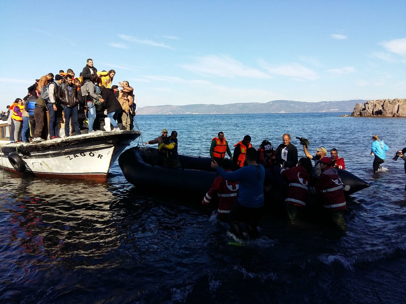 On the Aphrodite Hotel beach in 2015, a boat filled with refugees comes ashore from as volunteers come to help them.