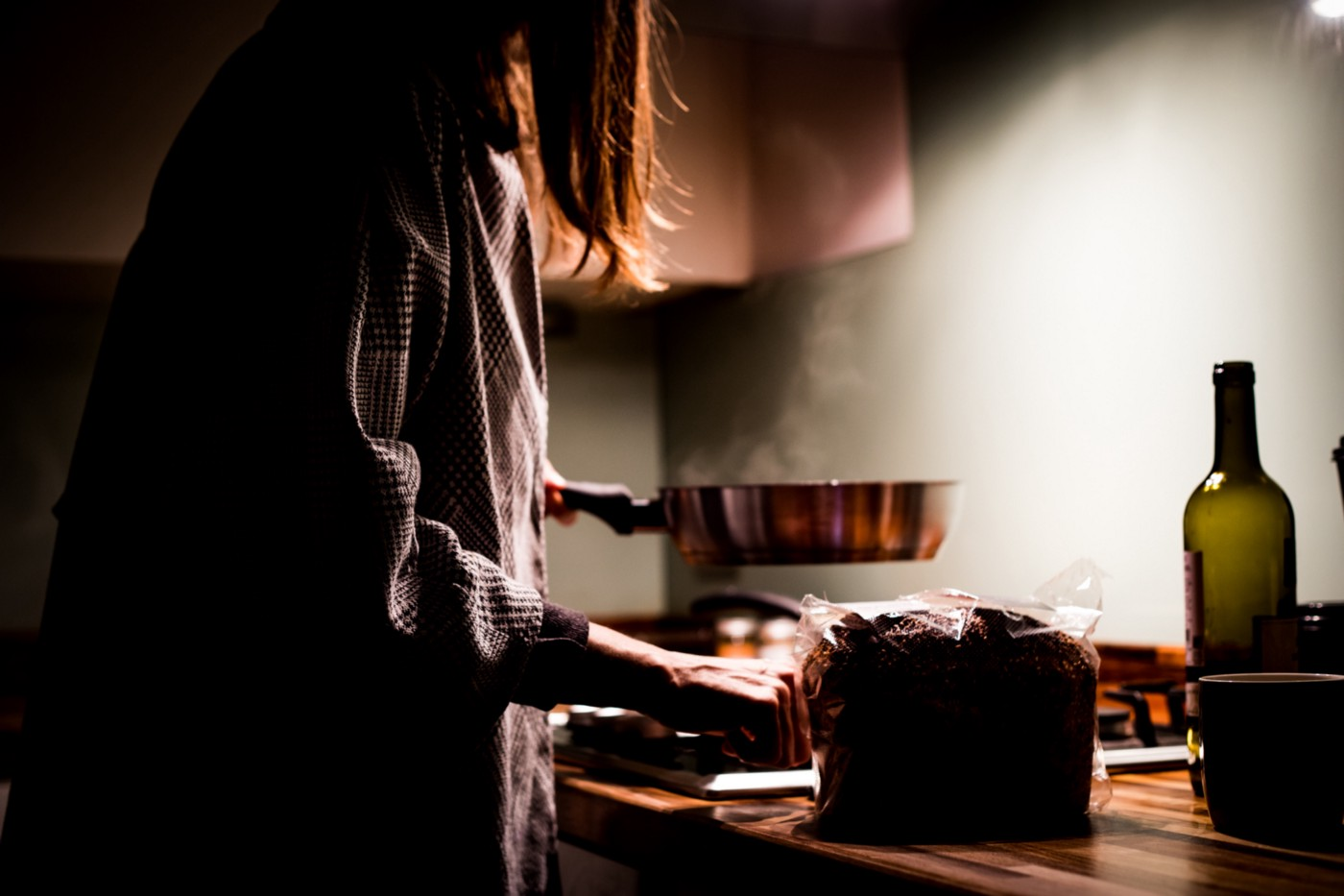 A dimly lit photo of a woman cooking on the stove top in her kitchen.