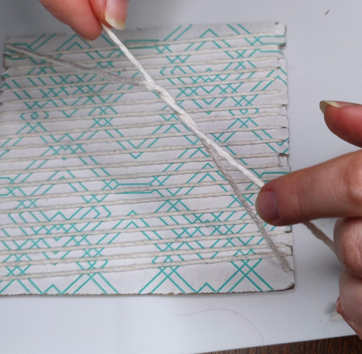Hands tying a knot at the back of a cardboard loom