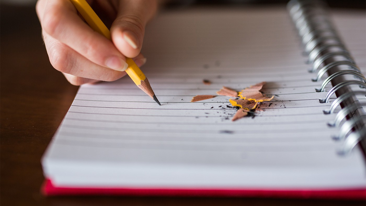 A person is writing in a notebook with a pencil. There are pencil shavings lying on the blank notebook page.