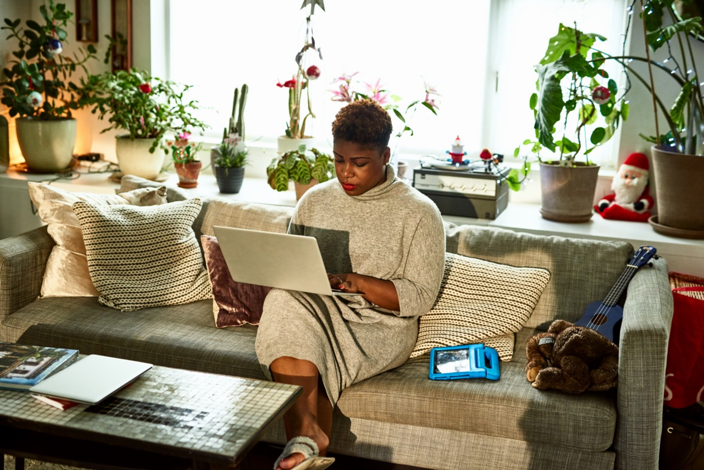 Black woman hard at work on her computer, sitting on her couch.