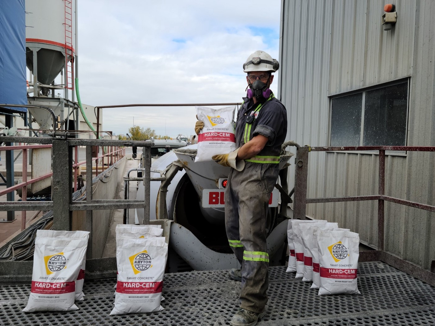 A construction worker is standing on a platform behind a ready-mix truck and holding a bag of the integral concrete hardening admixture, Hard-Cem, while being surrounded by several more bags that are lying on the ground.