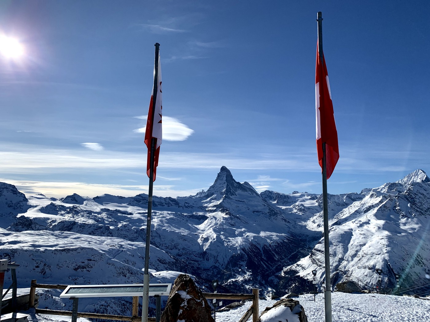 The Matterhorn in between a Valais canton flag and a Swiss flag