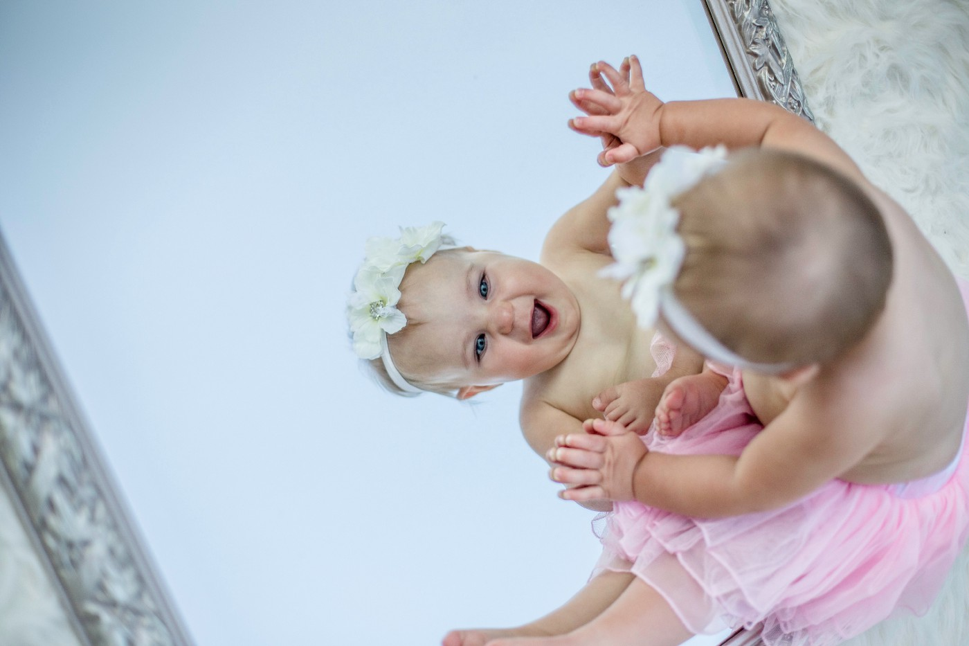 A baby dressed in a pink tutu and a flowery head-band delighting in her reflection in the mirror.