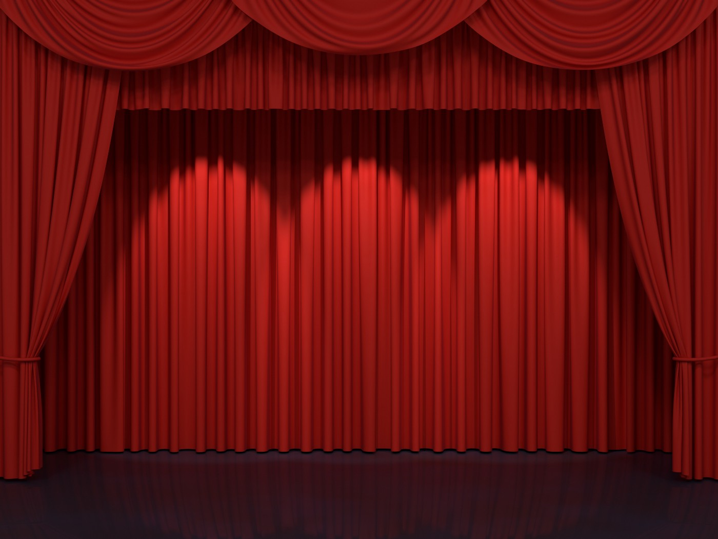Red curtains framing an empty stage