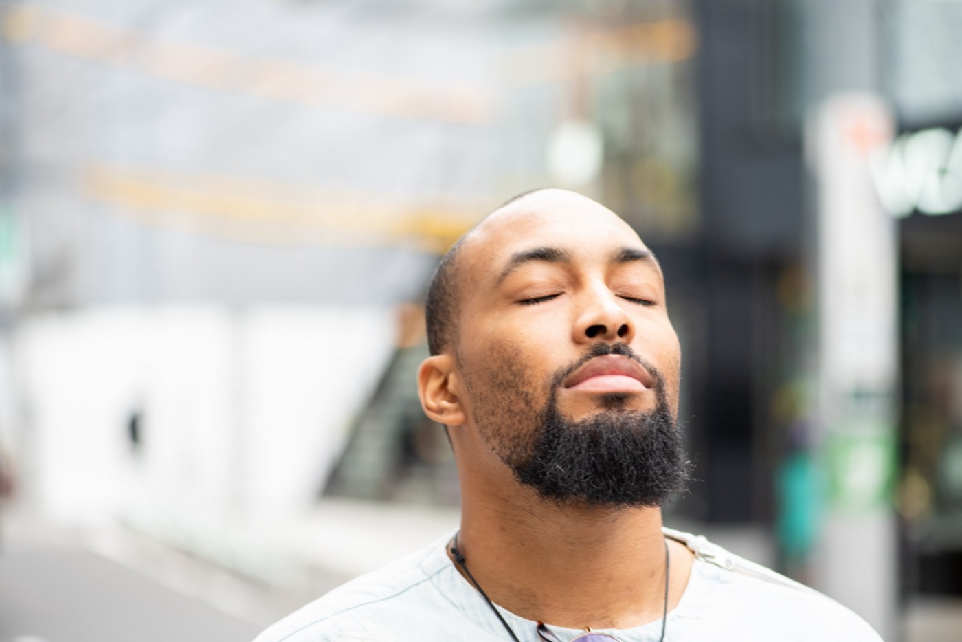 Young Black man closing his eyes with a peaceful expression.
