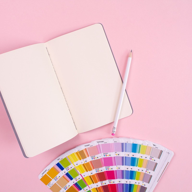 Photo of a notebook and printed Pantone colour cards sitting on a pink surface