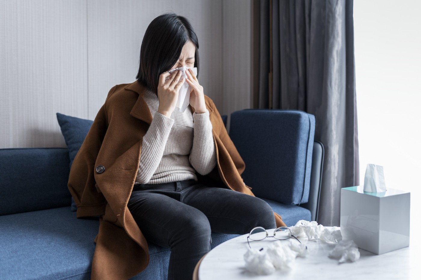 A woman sneezes into a tissue and wipes her nose.