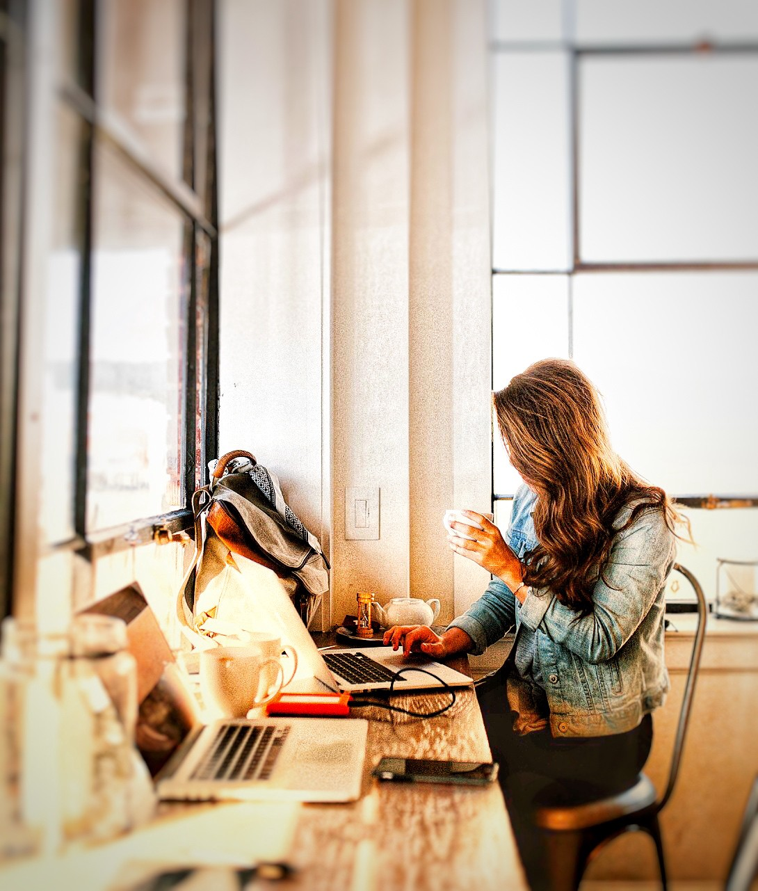 a woman sits at a desk at her laptop with a cup of tea in her hand.