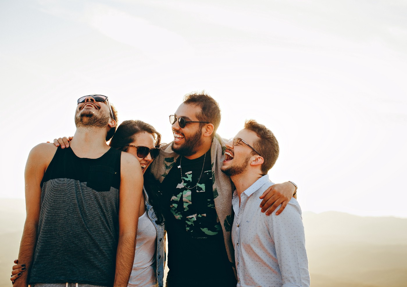 Four friends laughing and hugging with a white background