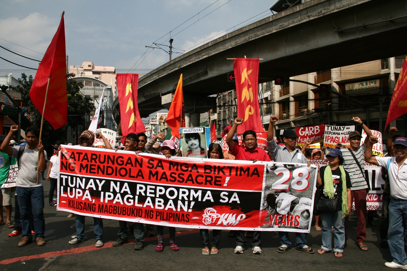 A crowd of protesters holding vertical red flags and carrying a large banner with Tagalog writing.
