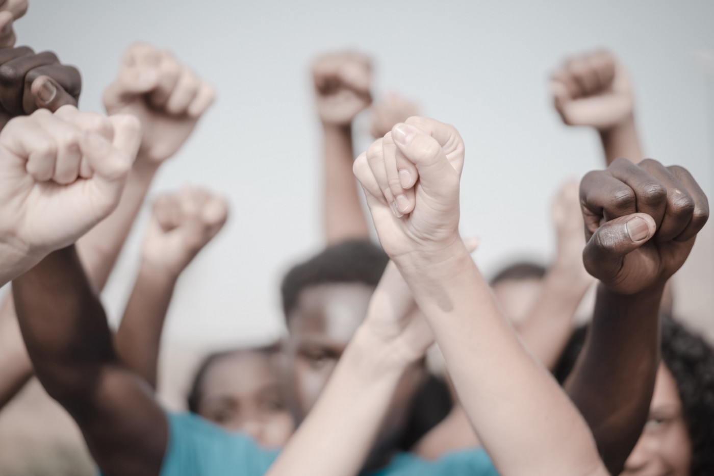 People of different races raising their fists.