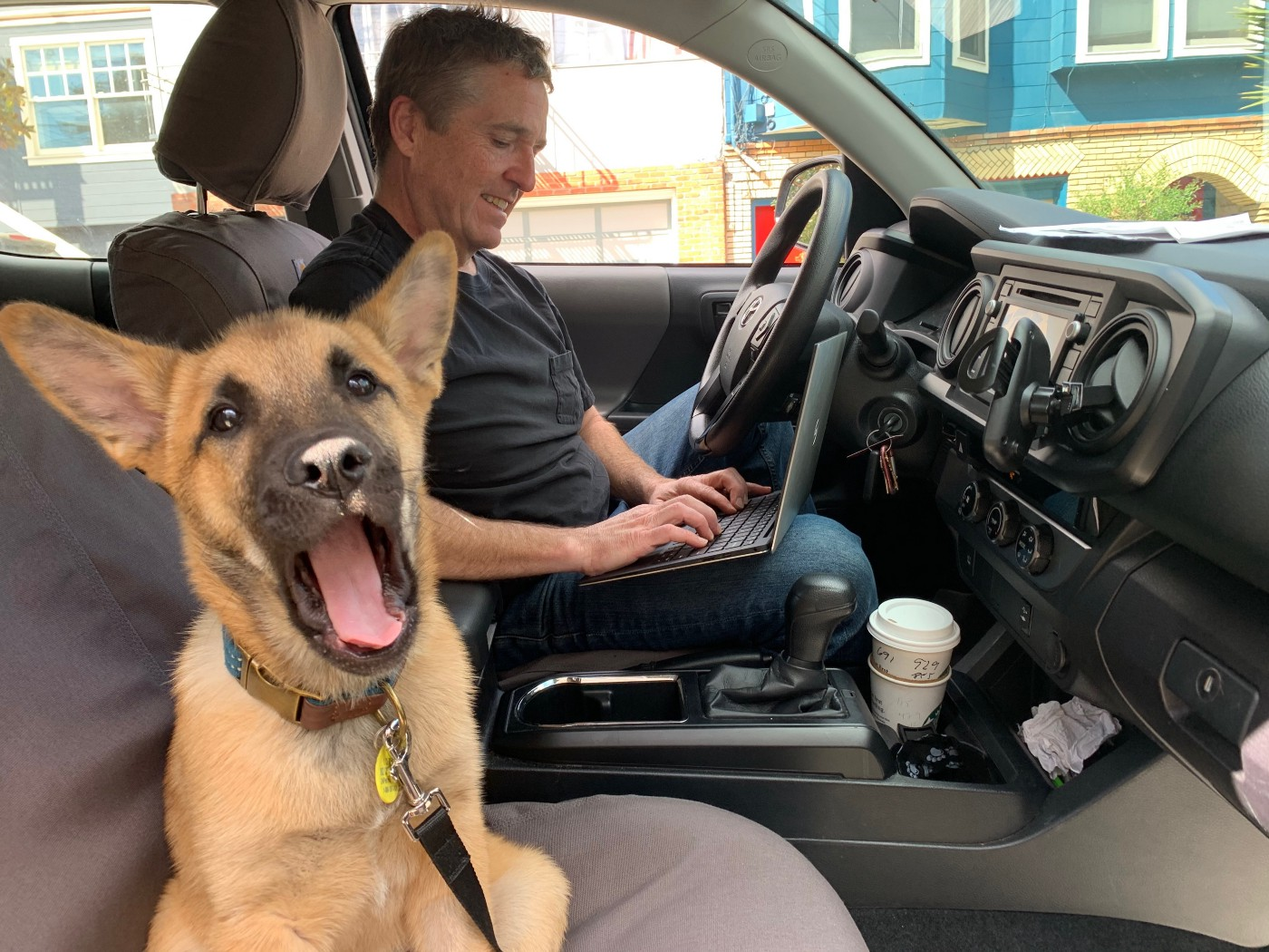 American Giant CEO Bayard Winthrop working on his laptop out of his truck with his 3-month-old puppy.
