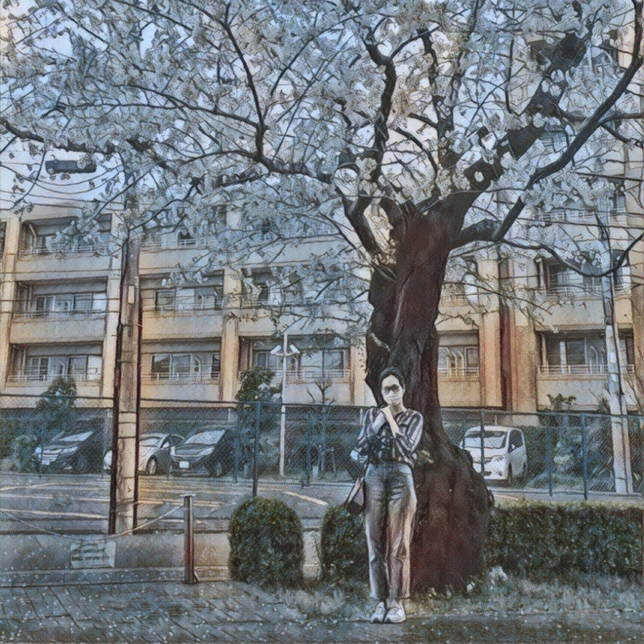 A masked woman standing beneath a flowering tree.