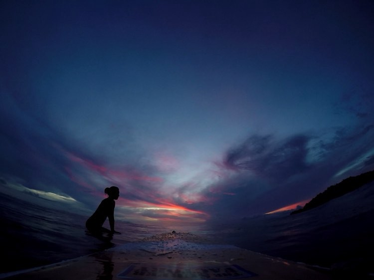 Sunset on a beach with dark blue skies and firey orange sun streaks, with a girl on her surfboard out on the line up