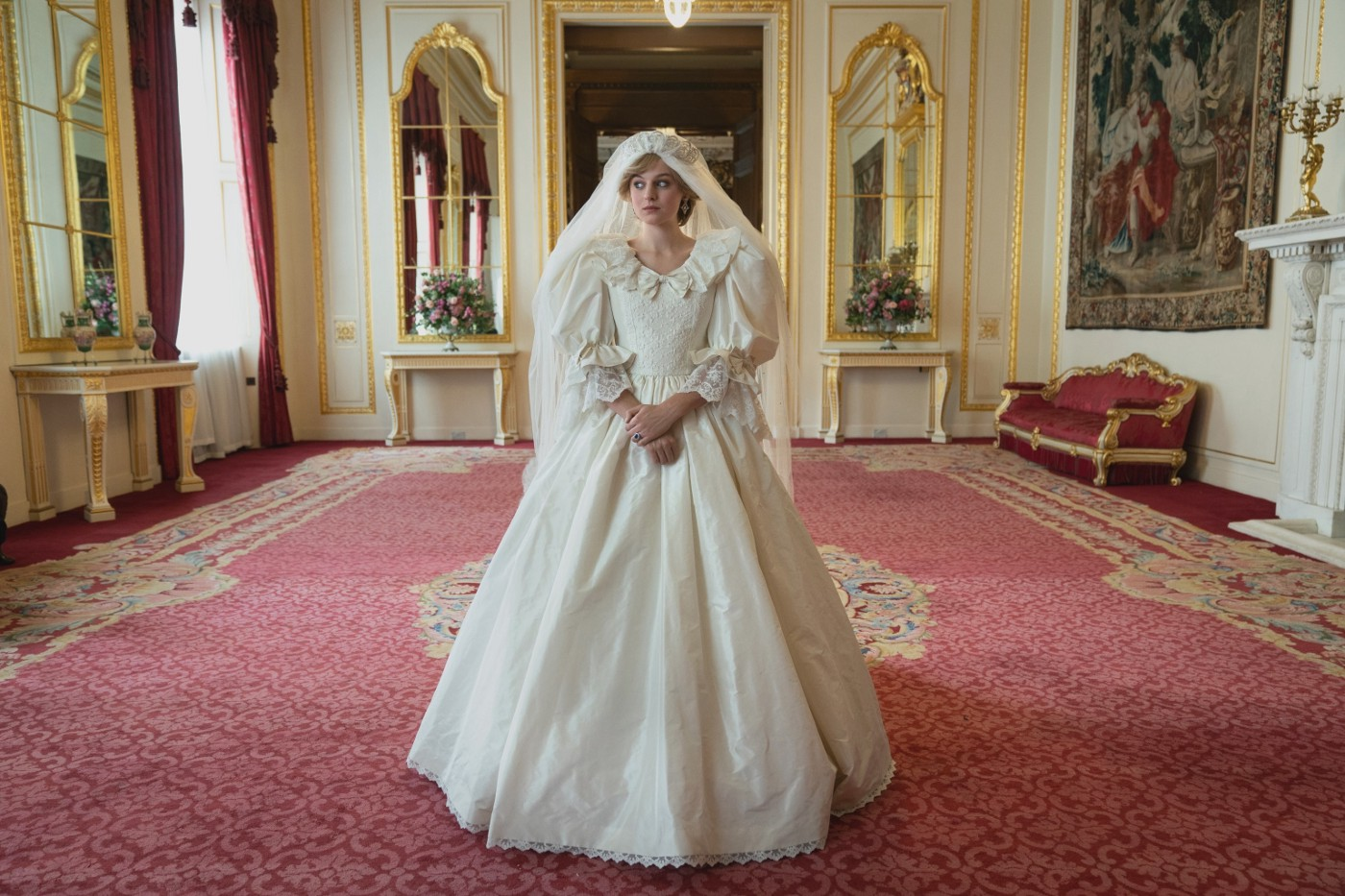 "Princess Diana (Emma Corrin) in a wedding dress in a large palace room in ""The Crown."""