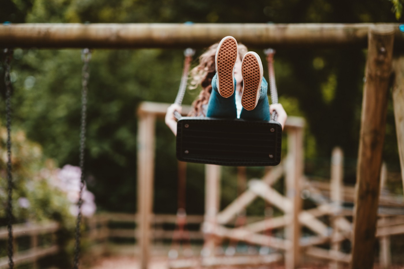 woman riding swing with trees in background. The swing is high so you can mainly see the bottom of the swing and her feet.