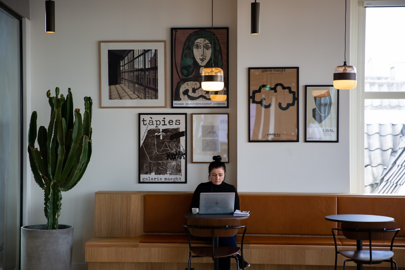 A woman sitting on a lounge area with a lot of frames on her background wall and working on her laptop