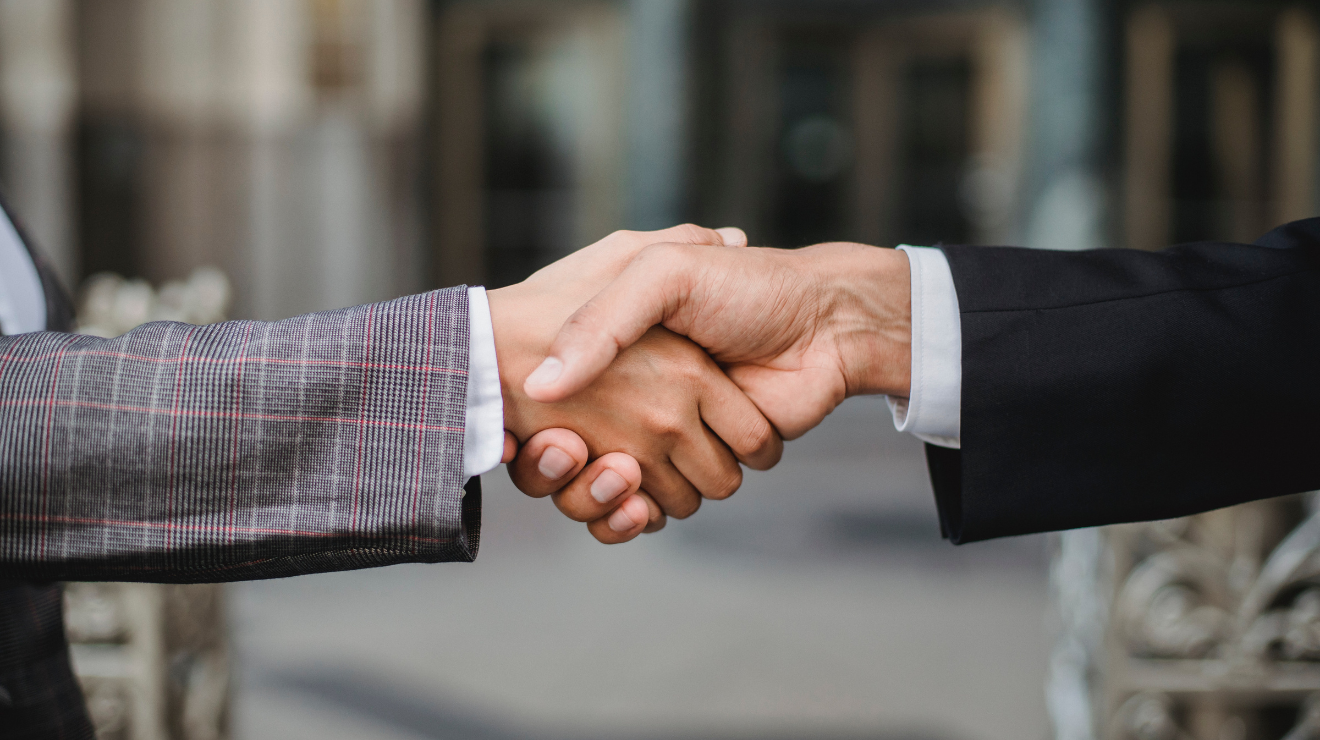 Close-up of a handshake between two men in suits