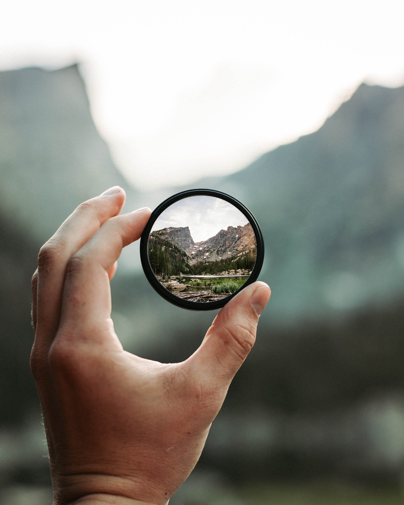 A man holds up a camera lens through which a beautiful landscape can be seen.