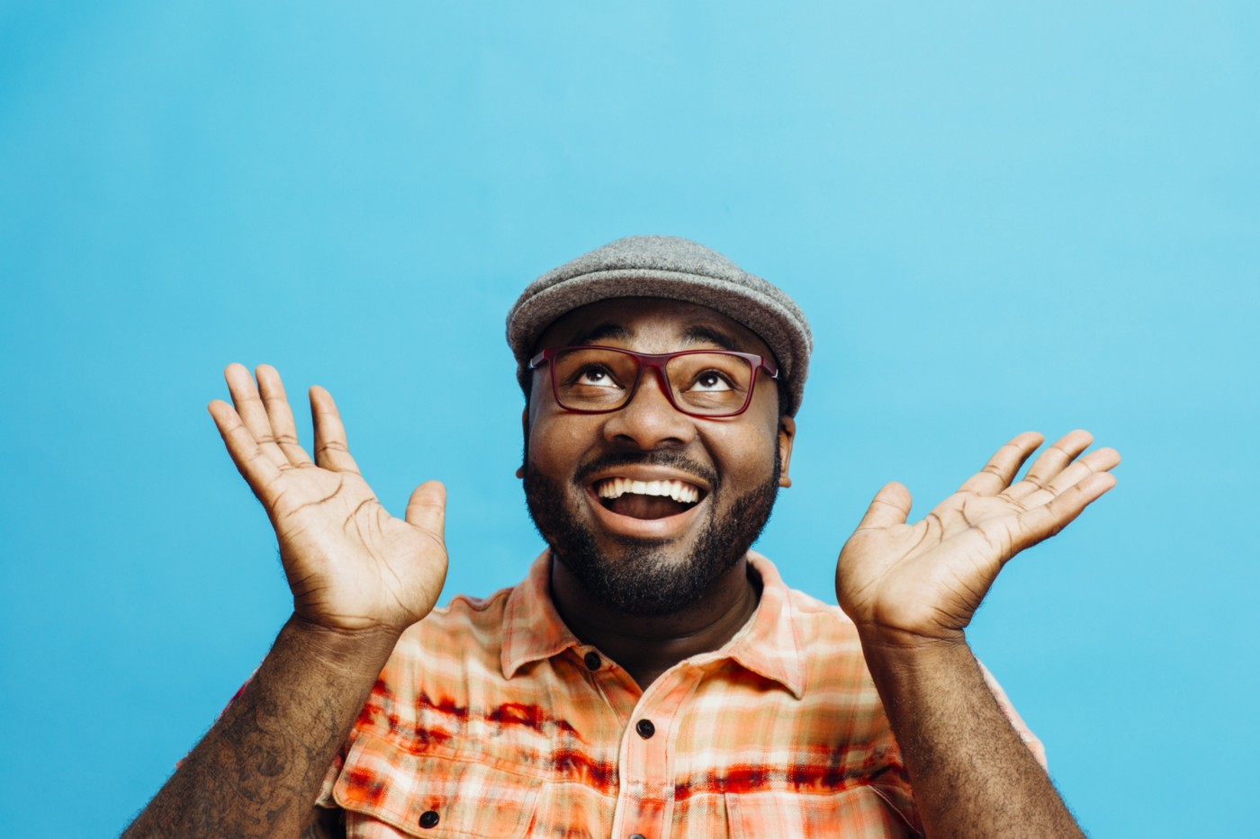 A photo of a man smiling with his eyes looking up towards the sky, jazz hands and all.
