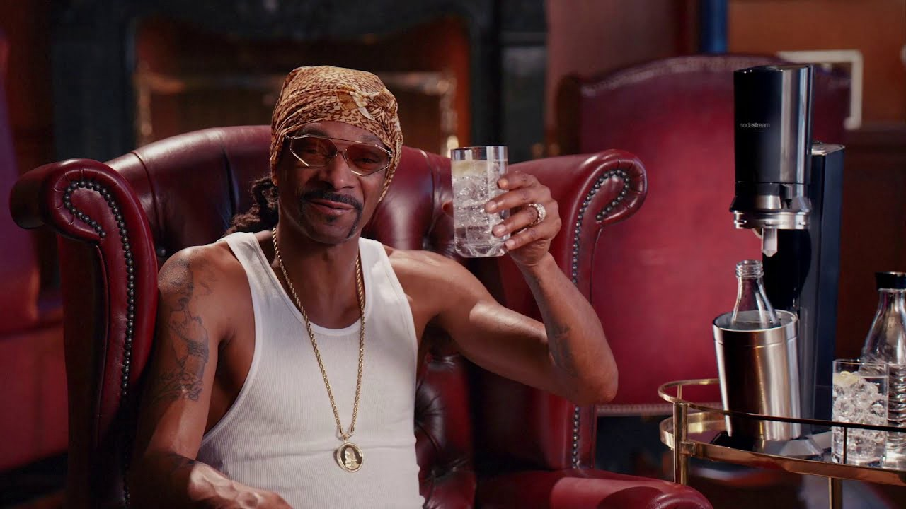 Image of Snoop Dogg holding up a glass of sparkling water.