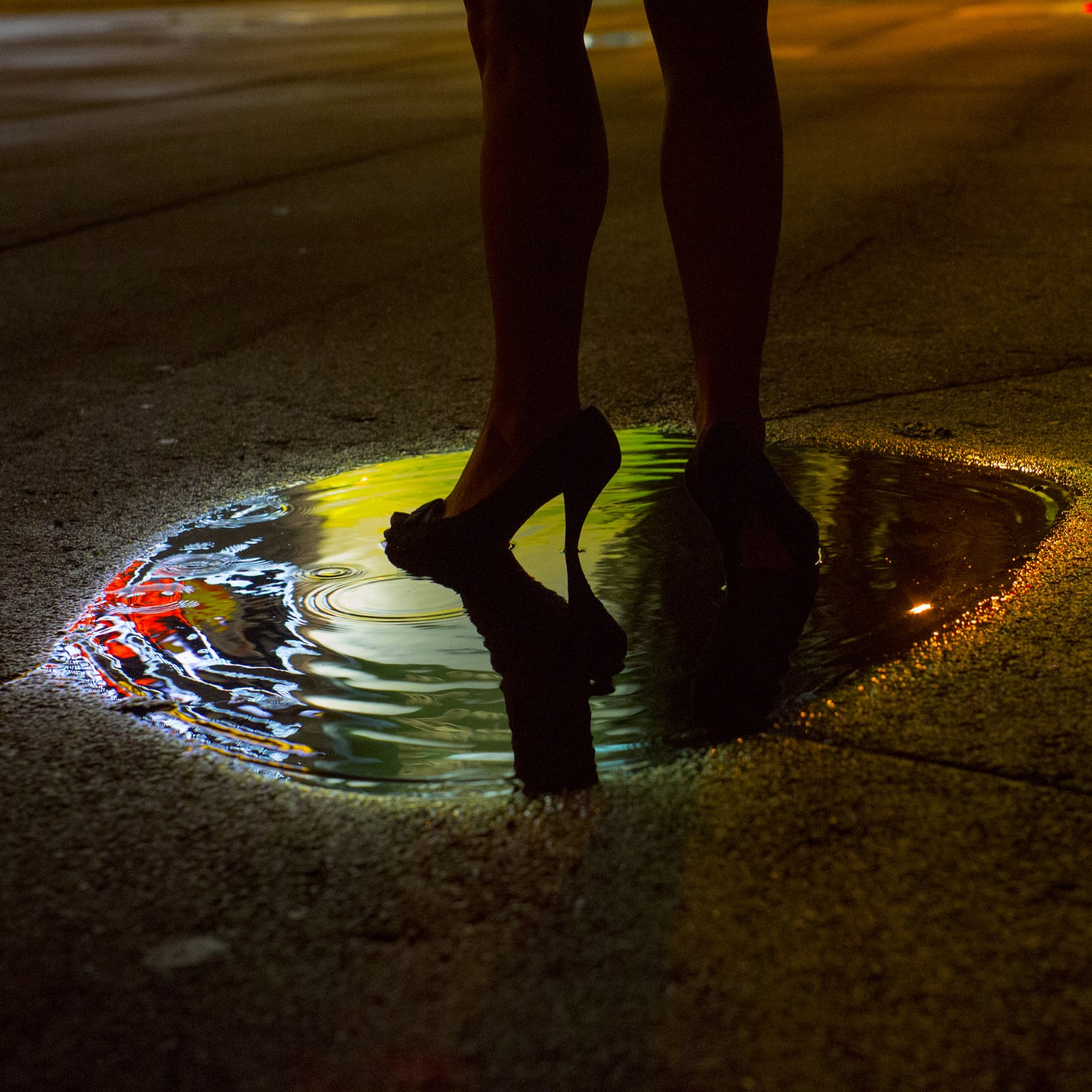 Person wearing high heels standing in a puddle at night.