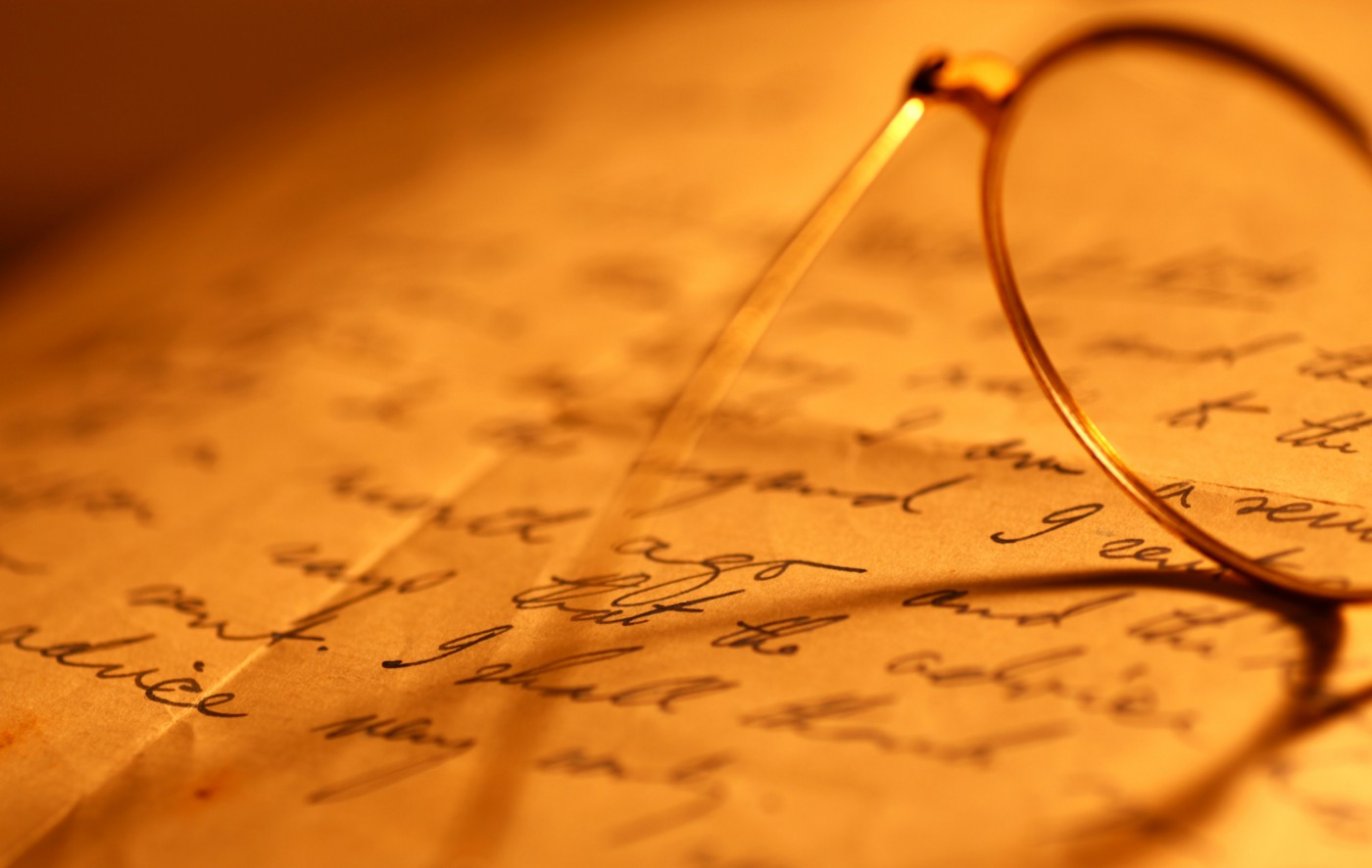 Closeup of glasses on a page scribbled with words.