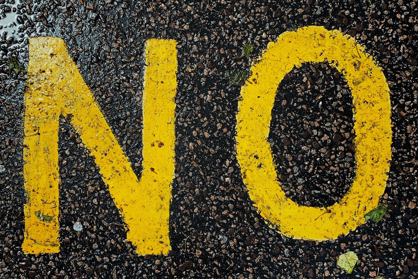 "yellow paint on wet blacktop spelling the word ""no"""