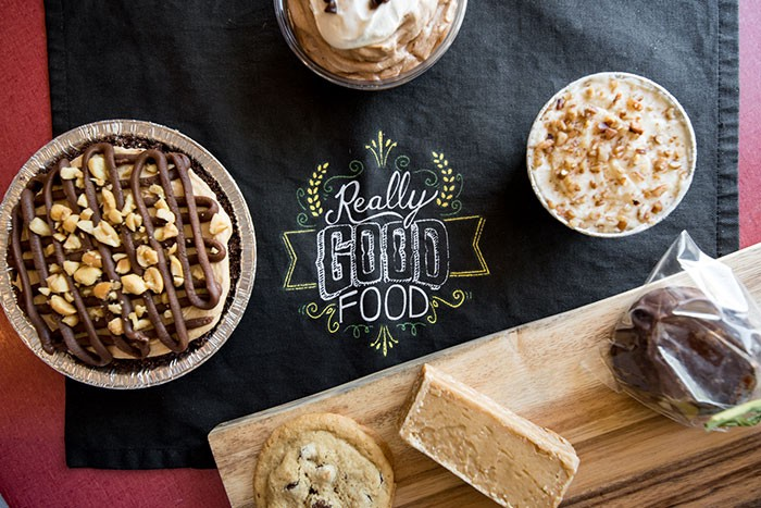 """A photo of a cloth with desserts that says """"good eats""""."""