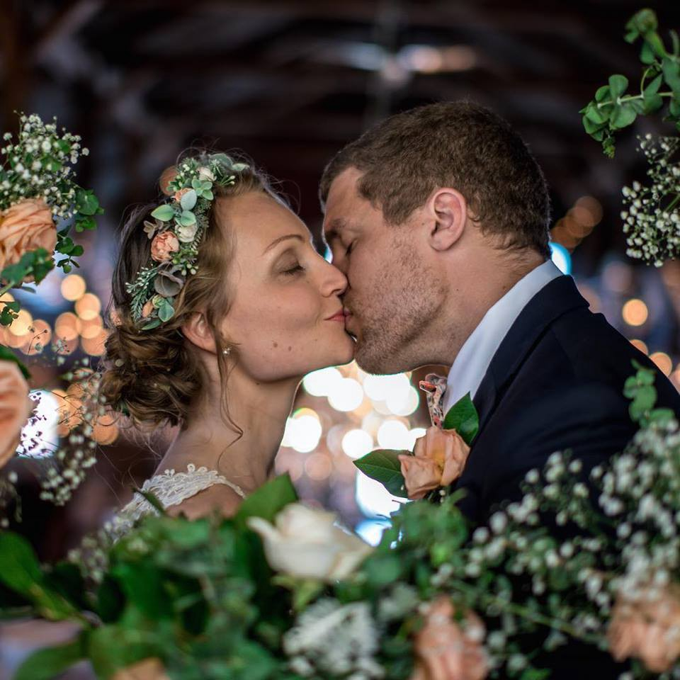 A bride and groom kiss with their eyes closed and framed by small white and peach colored flowers.