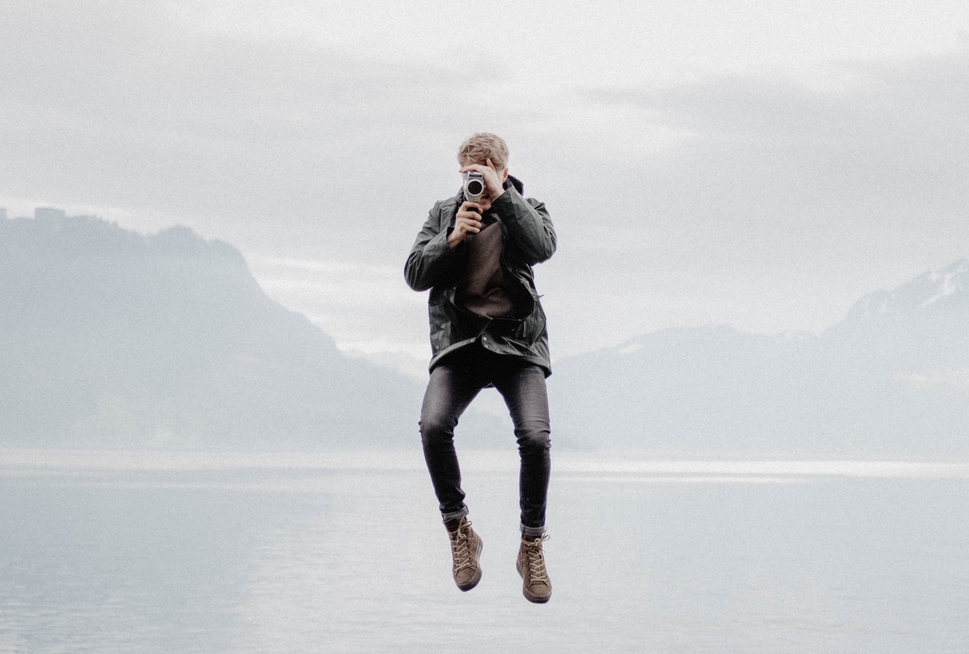 A man floating above water with an old camera in his hands.