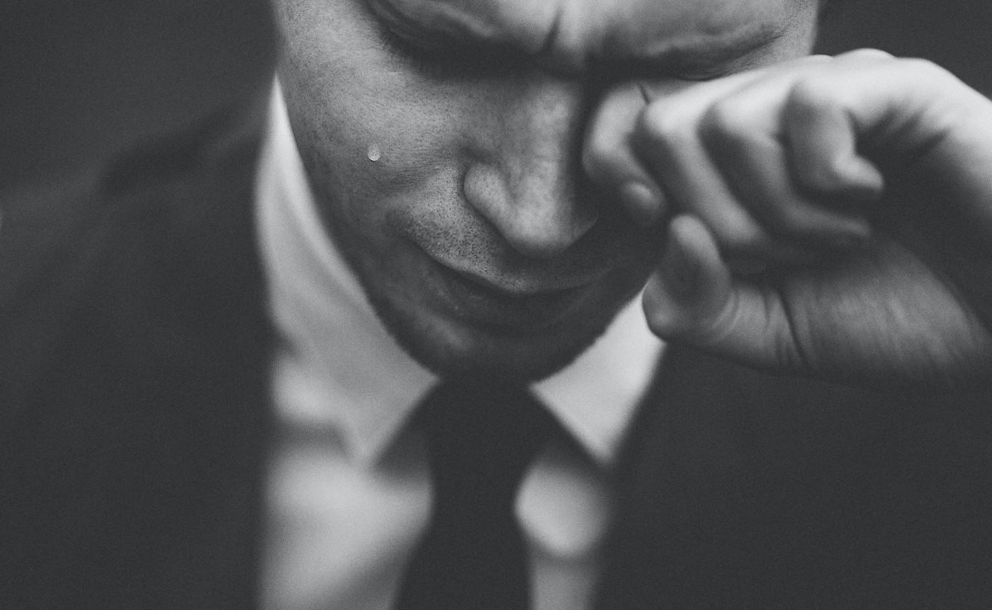 Man, in suit with head bowed, crying.