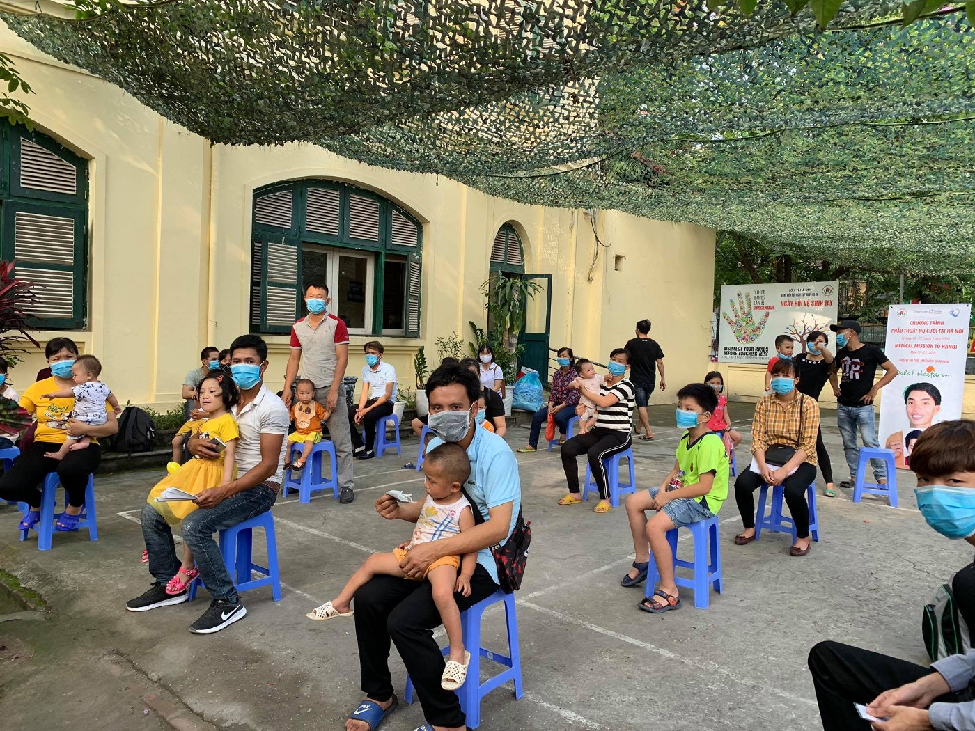 Patients and families sitting six feet apart during screening day at a medical mission in Vietnam.