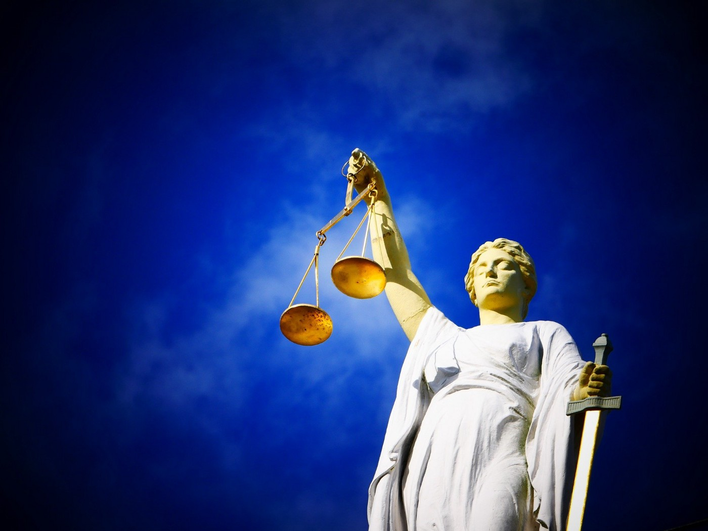 Lady justice holding the scales of justice in her right hand and a sword in her left, set against a blue sky background.