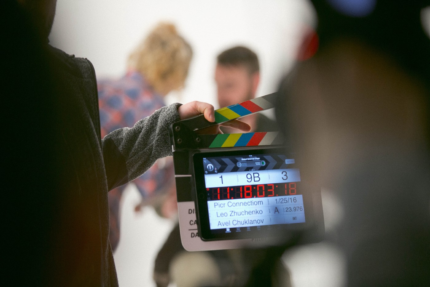 "blurred people with one person holding a directors slate that is about to come down marking that the year is ""a wrap"""