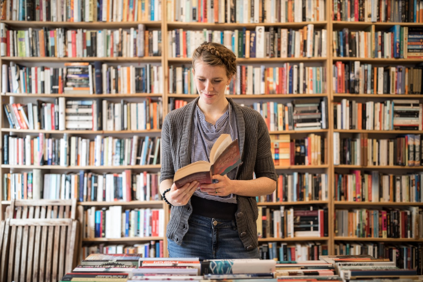 A young female customer  at bookstore standing against a bookshelf picks up a book and reads through it.