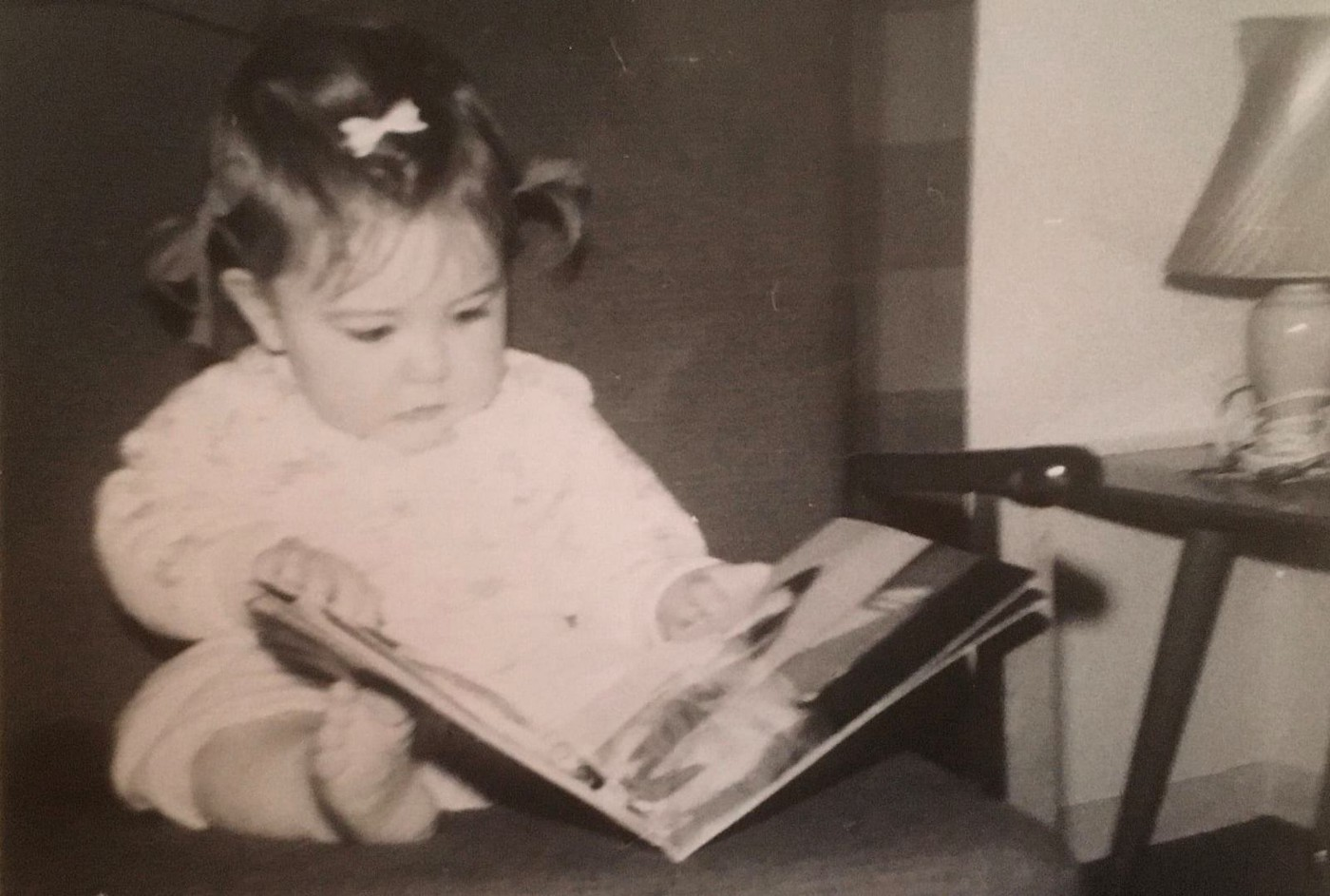 Image of author as a baby reading a book