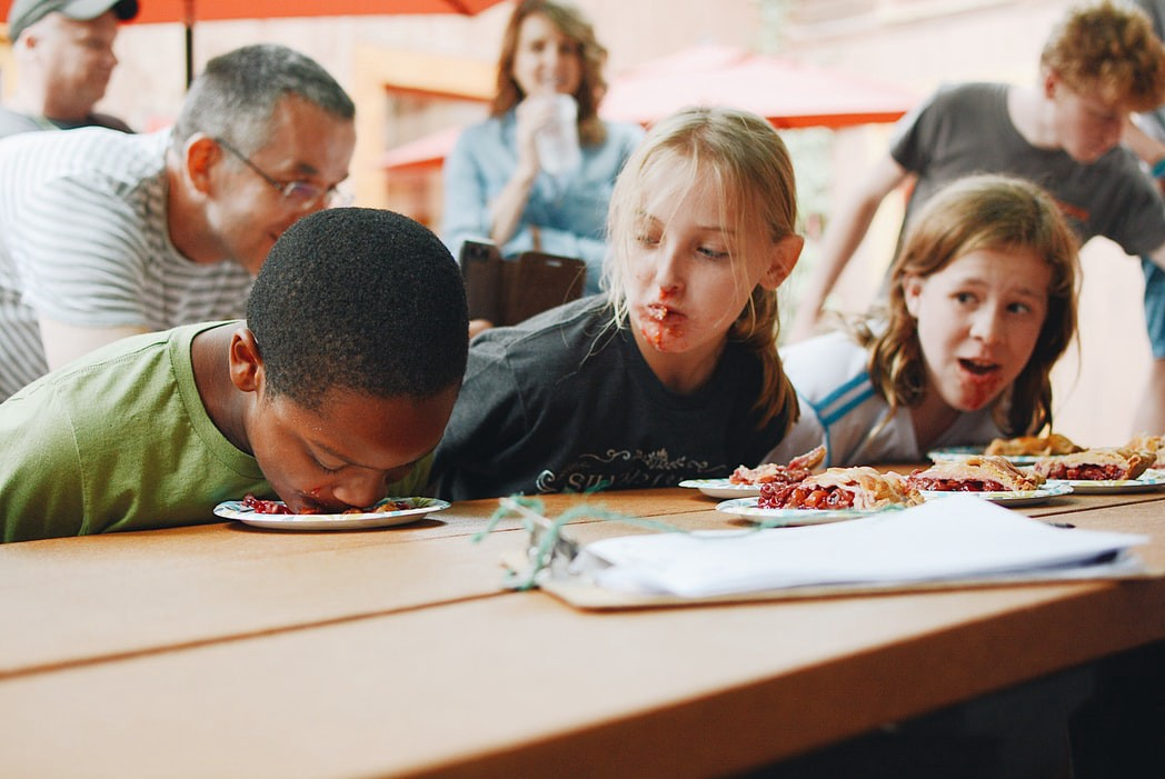 Three kids sitting at a table in a pie eating contest with their hands behind their backs and pie on their faces. One is face down in the plate and the other two are looking at him.