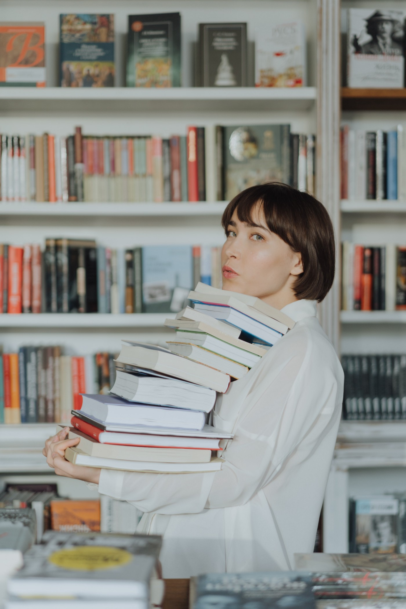 Light-skinned woman wearing white blouse with brown bob carrying a pile of 10+ books in a library or book shop.
