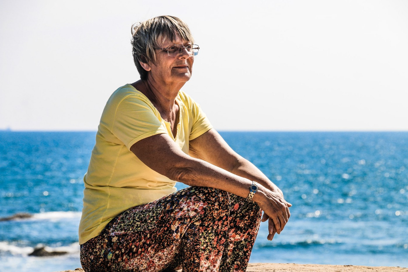 Older woman with glasses sitting on a beach with ocean behind her.