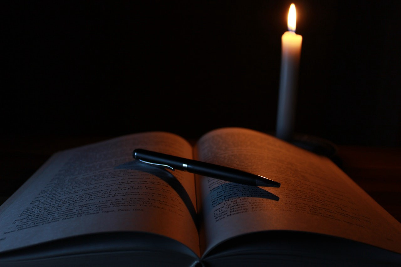 Dark room with one lit candle near an open book with a pen lying on the book diagnally.