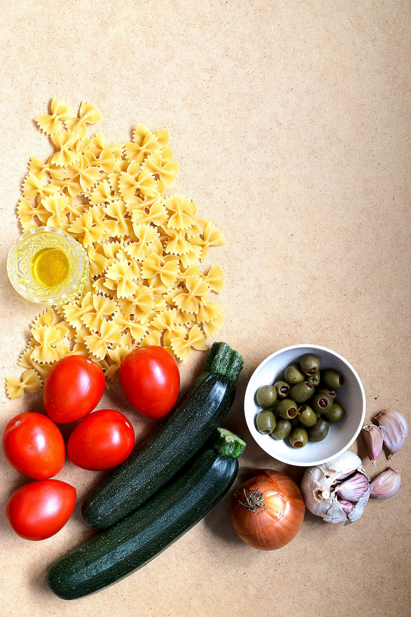 bow tie pasta, olive oil, tomatoes, zucchini, olives, garlic and onion