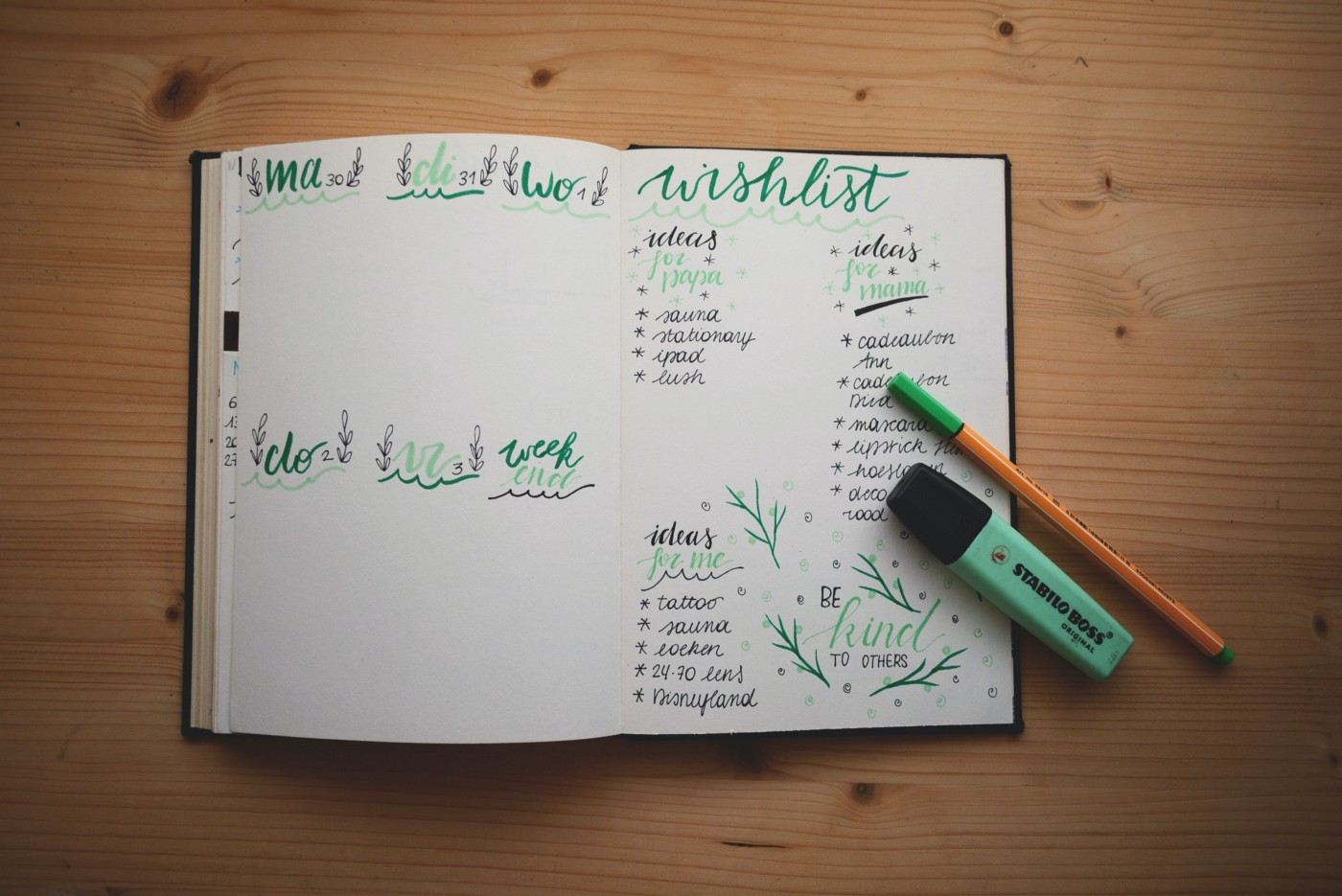 A notebook open that has some handwriting in it, the pages having green colored text on it, there is a pencil and highlighter sitting on the viewer's right of the page